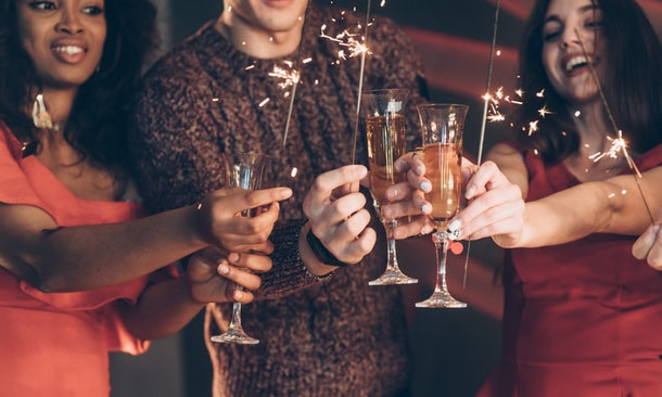 Half burned out. Multiracial friends celebrate new year and holding bengal lights and glasses with drink.