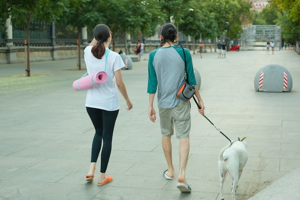 A young couple walks their dog, coming back from yoga, carrying their mats.