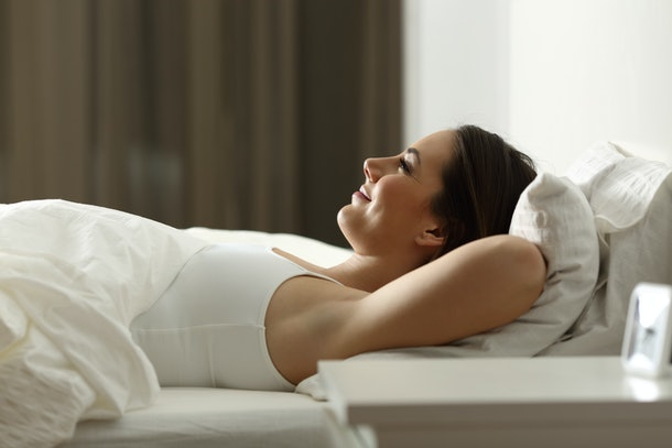 Side view portrait of a happy woman relaxing sleeping on a bed at home in the night