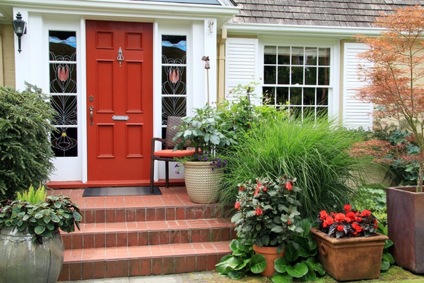 Charming small home with red front door and summer garden containers filled with annual flowers. Photo taken from the public sidewalk.