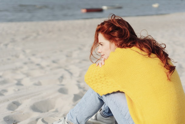 Lonely young woman sitting alone on a sandy beach with her chin resting on her knees staring out over the ocean with a pensive expression