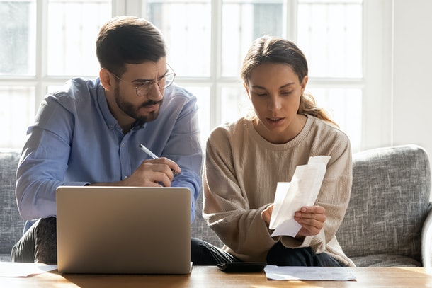 Serious couple calculating expenses, bills together, using laptop, sitting on couch at home, checking documents, confused man and woman planning budget, discussing loan or debt problem
