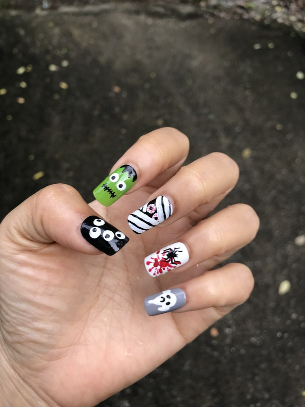 Long, square-shaped nails feature nail art that looks like eyeballs, Frankenstein's head, a mummy, a spider, and a ghost.