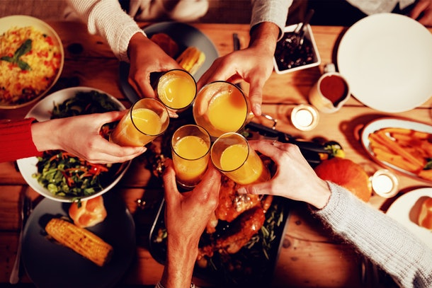 Overhead view of the hands of a group of young adult multi-ethnic male and female friends sitting at a table at home set for Thanksgiving dinner making a toast with glasses of orange juice