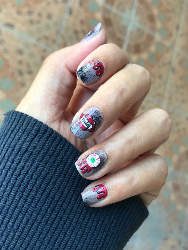 Short square-shaped nails feature designs of dripping blood, vampire fangs, and an eyeball.