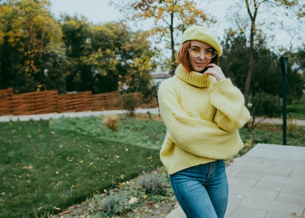 Outdoor fashion photo of young beautiful lady surrounded autumn leaves.Autumn woman in autumn park. Warm weather. Fall concept.Close up image of happy red hair woman in sunglasses and autumn clothes