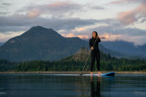 Adventurous Girl on a Paddle Board is paddling in a calm lake with mountains in the background during a colorful summer sunset. Taken in Stave Lake near Vancouver, BC, Canada.