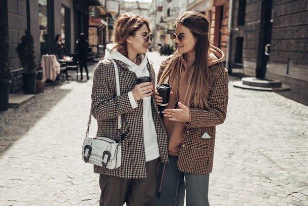 Two best friends in hoodies and plaid jackets are standing in the street with pumpkin coffee in to-go cups in their hands.