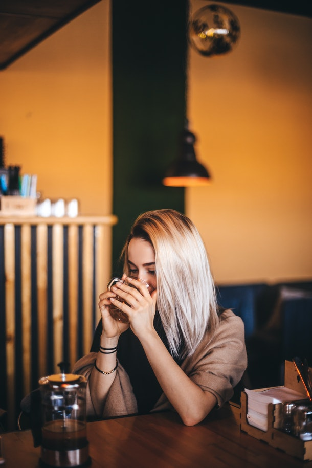 A blonde girl sips pumpkin coffee in a chic restaurant with a yellow wall.