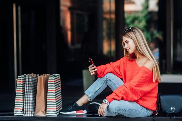 Beautifulblonde woman sitting on a street and surrounded by shopping bags and looking on phone.