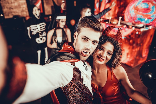 Young Couple in Halloween Costumes taking Selfie. Beautiful Woman and Handsome Young Man Wearing Costumes having Fun at Halloween Party in Nightclub. Happy Friends having Fun Celebrating Halloween