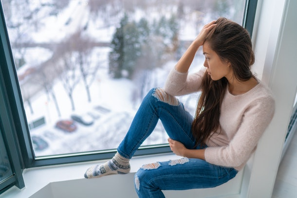 Winter depressed sad girl lonely by home window looking at cold weather upset unhappy. Bad feelings stress, anxiety, grief, emotions. Asian woman portrait.