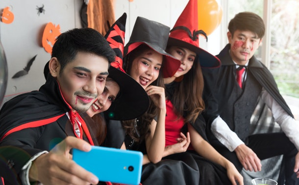 Young group of Asian people in spooky and scary costume taking selfie in Halloween party