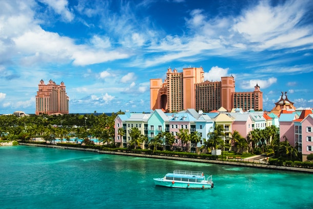 Beautiful scene of a boat, ocean, colorful houses and a hotel in Nassau, Bahamas on a summer sunny day
