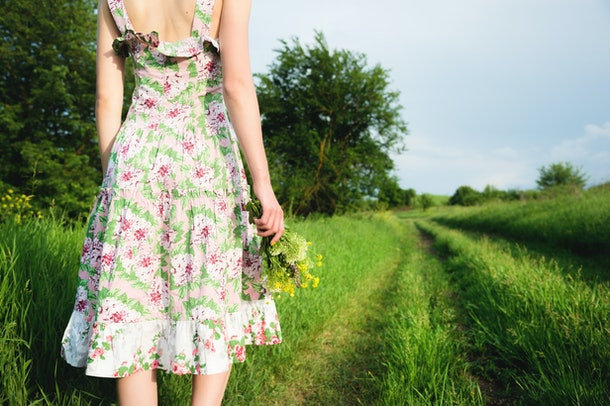 A view from the back of a girl in a light summer dress with a bouquet of wildflowers is standing in front of a country road. The concept of feminism of equal rights and independence of women