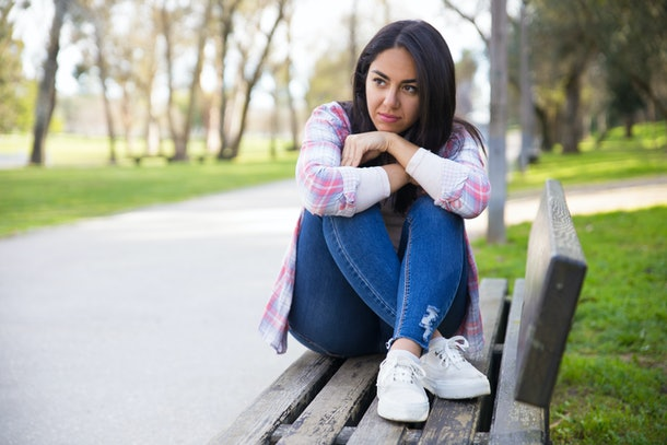 Pensive young woman contemplating in park. Serious sad mixed race girl sitting on bench and looking into distance. Introspection concept