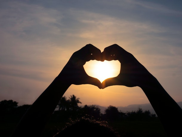 Silhouette hands in the heart shape on sunset background. concept love valentine day.