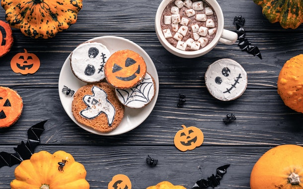 A plate of Halloween cookies on a black wooden table is next to a mug of hot cocoa topped with marshmallows and surrounded by small pumpkins.
