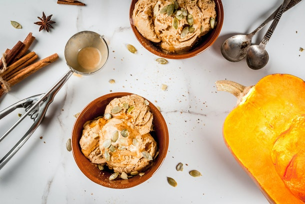 Pumpkin ice cream with pumpkin seeds on top sits in a bowl on a table next to ingredients and kitchen utensils.