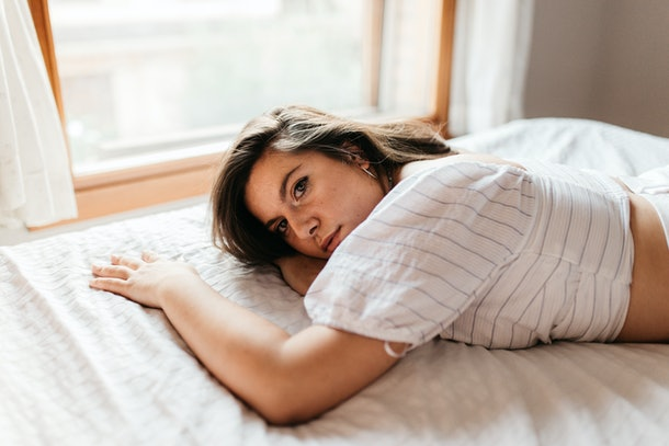 Pensive and attractive sad woman lying on the bed. Thinking about problems. Copyspace. Feeling worried, hurt, heartbroken lonely