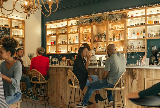 Smiling young African American couple sitting at the counter of a bar talking and having drinks while on a date together