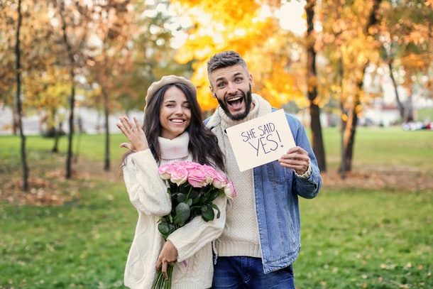 A happy couple poses for their engagement announcement showing off the ring in an autumn park.