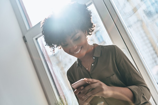 Texting. Attractive young African woman using her smart phone and smiling while sitting on the window sill indoors