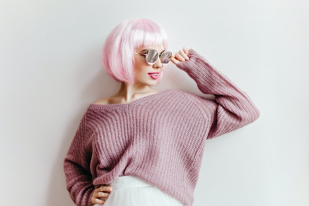 Confident girl with light-pink hair touching her glasses with smile. Indoor photo of good-looking young woman with trendy periwig enjoying photoshoot.