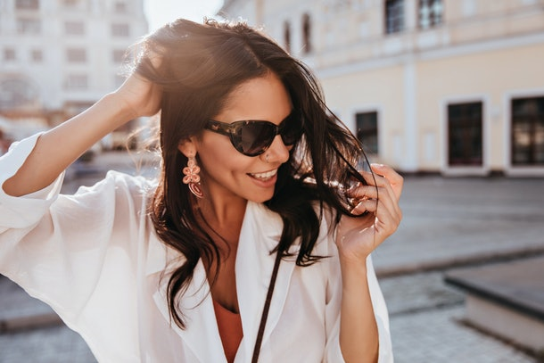Amazing brunette woman in trendy earrings smiling on city background. Wonderful tanned girl in sunglasses enjoying good day.