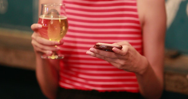 Woman holding beer and cellphone smartphone device at bar