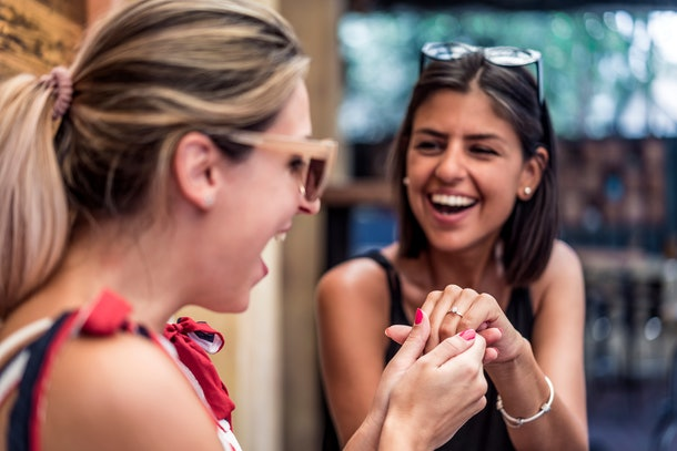 A woman shows off her engagement ring to her friend while smiling.
