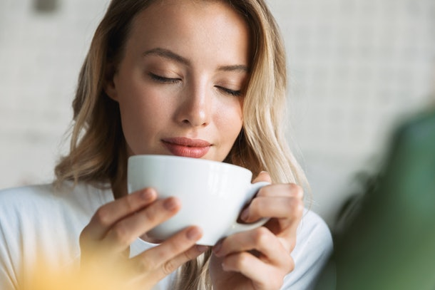Close up of a beautiful young blonde woman sitting at the cafe indoors, drinking coffee