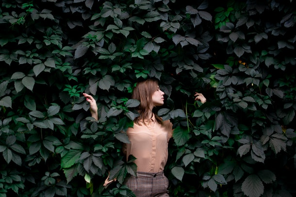 young attractive girl stands in green leaves alone with nature, a woman touches plants and dreams, a concept of a man in nature