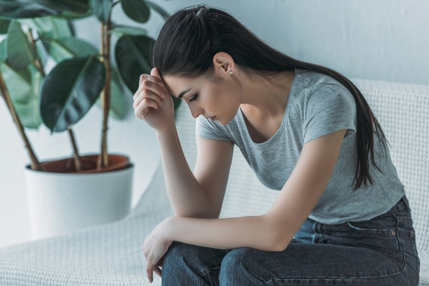 frustrated young woman in depression sitting on couch and looking down
