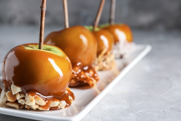 Delicious caramel apples with tree branches on plate