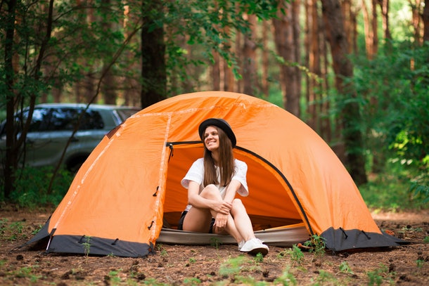 Young woman resting in hat near camping tent in wilderness. Rest concept