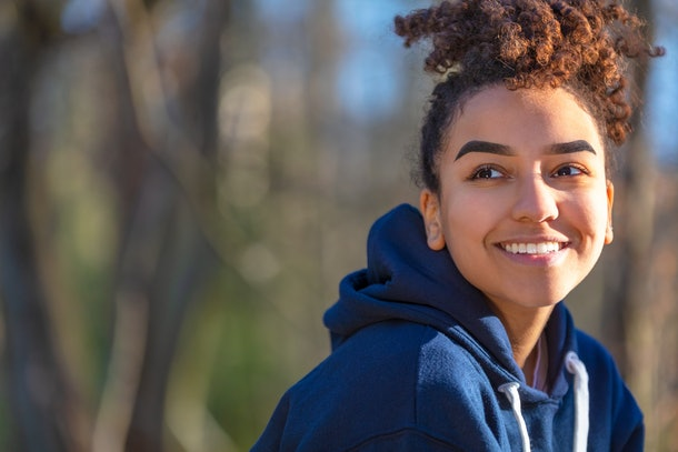 Outdoor portrait of beautiful happy mixed race biracial African American girl teenager female young woman smiling with perfect teeth wearing a blue hoodie