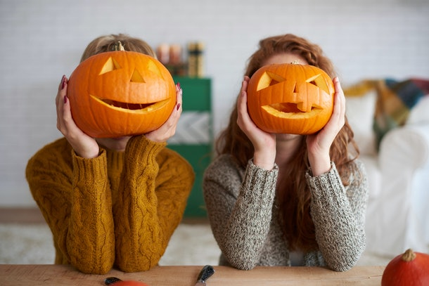 Two women wearing sweaters and holding pumpkins in front of their faces is a cute picture idea for Instagram captions for pumpkin carving.