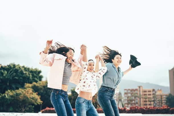 Happy Asian girls jumping together outdoor - Young women friends having fun during university break dancing and celebrating outside - Millennial generation, friendship and youth people lifestyle