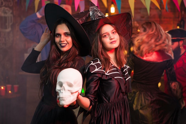 Portrait of two witches celebrating friendship at a halloween party. Halloween costume.