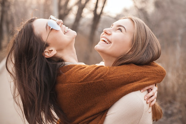 Two young women laughing and hugging outside in the fall are striking a great pose for fall puns for Instagram captions.