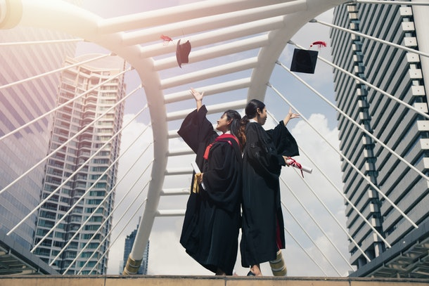 two asian female graduated students celebrate success by throw cap into the air