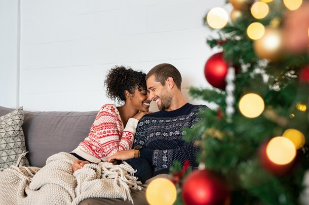 A happy couple relaxes on a comfortable couch wearing holiday sweaters near a Christmas tree.