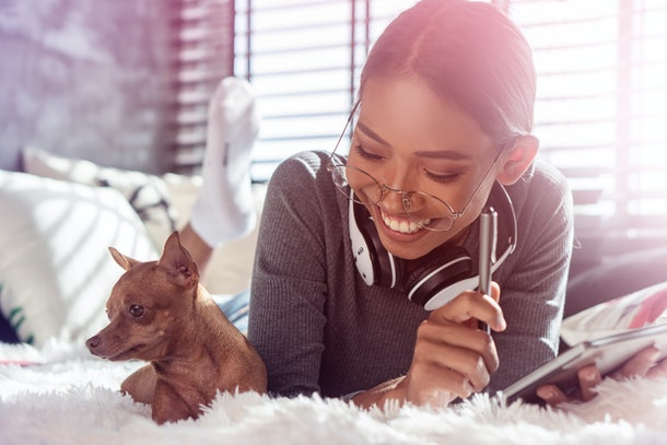 Beautiful smiling girl with headphones and tablet relaxing with her dog on a bed at home. People, comfortable lifestyle and leisure concept