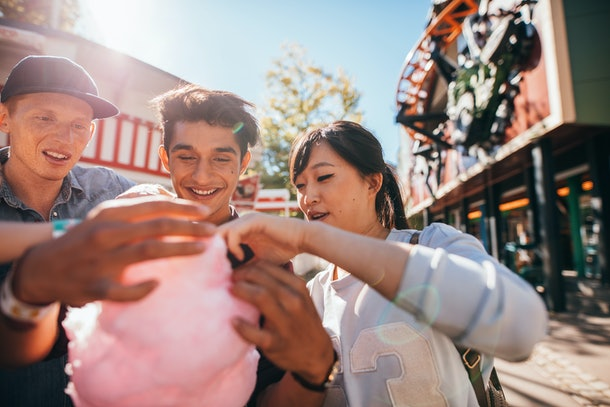 Young men and woman sharing cotton candy floss at fairground. Group of friends eating cotton candy in amusement park.