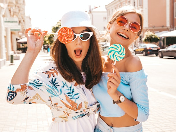 Two young beautiful smiling hipster girls in trendy summer clothes and panama hat. Sexy carefree women posing on street background.Positive models having fun in sunglasses.Eating candy lollipop