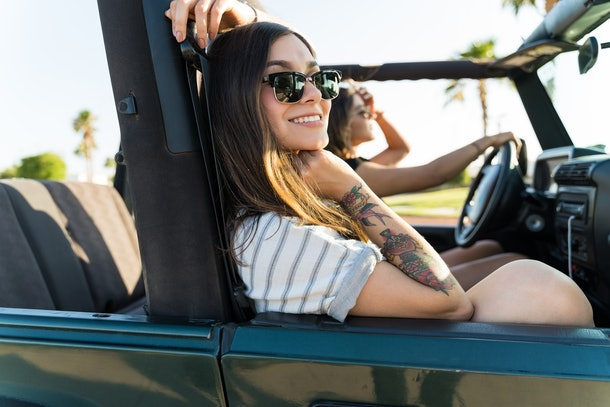 Happy Hispanic woman traveling with friend in 4x4 during summer