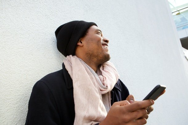 Close up portrait of handsome young african american man laughing with cellphone by white background and looking away