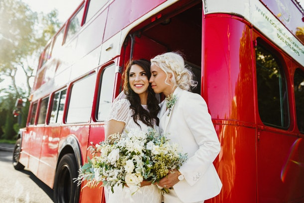 A couple stands next to a red double-decker bus with a bouquet of flowers during their holiday wedding.
