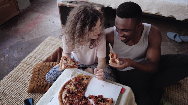A happy couple sits on the floor hugging and eating pizza for date night.